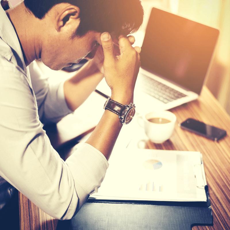 Man achter laptop burnout vermoeid